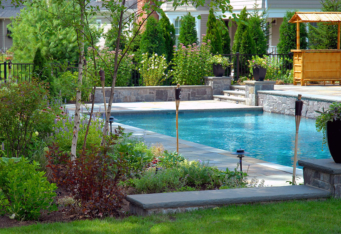 GA Landscape Design in-ground pool with stone and mature plantings create a backyard oasis in this NJ landscape