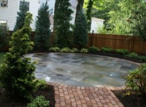 A beautiful stone and brick circular patio lead to by a brick walk, in a Maplewood NJ backyard