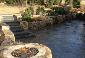 A gas fire pit, and built in stairs leading to the rest of the landscape complete this gorgeous natural stone patio