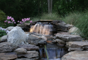 Landscape lighting lights up the waterfall in this landscaped backyard