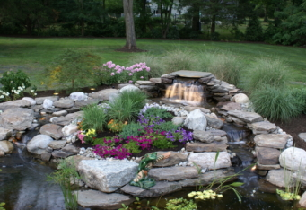 Landscape lighting lights up the waterfall in this backyard landscape