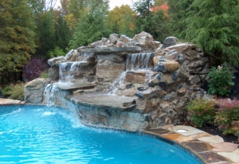 Custom Waterfall into a pool surrounded by large plantings in this Scotch Plains NJ backyard