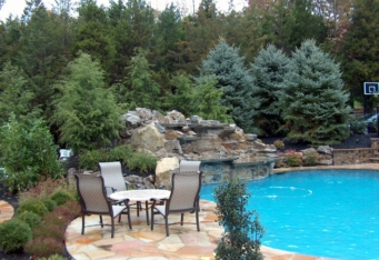 A Waterfall into a pool in this Scotch Plains NJ landscaped backyard