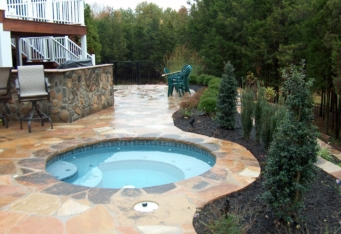A hot tub surrounded by plantings for privacy in this backyard design