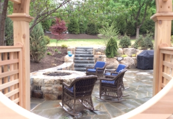 Basking Ridge NJ Stone Fire Pit with seating area in this backyard design
