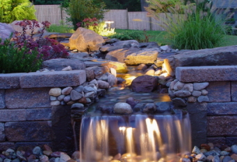 Landscape Lighting lights up a beautiful water feature completing the landscaping of this home
