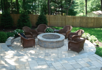 Custom Fire Pit with seating complete this backyard landscape design in Clinton NJ