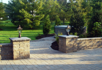 Paver wall with Columns and Lighting complete the entrance to the hot tub in this landscape
